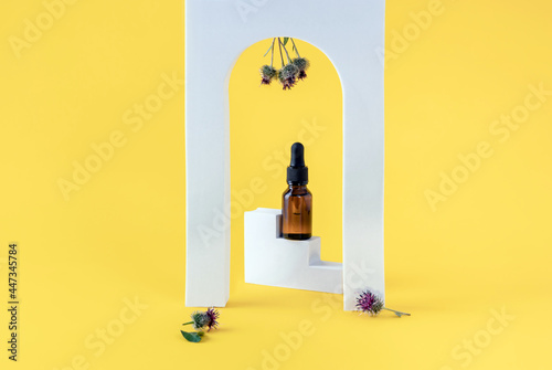 burdock oil in a glass bottle and burdock flowers on a yellow background with ge Fototapet