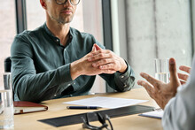 Focused Executive Businessman Client Clasped Hands Negotiating, Thinking, Making Decision Sitting At Table Listening Manager Partner At Office Negotiations Meeting. Business Interview Concept. Closeup