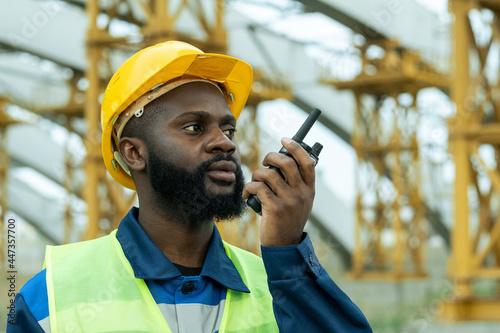 Billede på lærred African construction worker in work helmet talking in transmitter while working