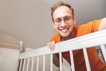 Young Happy Caucasian Father Looking At His Baby In Crib