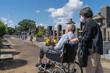 車椅子に乗った夫を介助しながらお盆の墓参りに向かうマスクをした老夫婦。暑い日差しの照り付ける夏の日に、花を持って墓地を進む(横)
