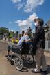 車椅子に乗った夫を介助しながらお盆の墓参りに向かうマスクをした老夫婦。暑い日差しの照り付ける夏の日に、花を持って墓地を進む(縦・日差し)