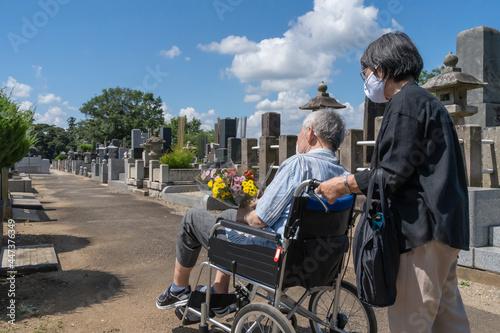 車椅子に乗った夫を介助しながらお盆の墓参りに向かうマスクをした老夫婦。暑い日差しの照り付ける夏の日に、花を持って墓地を進む(横) Fototapeta