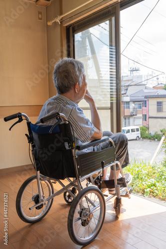 Fotografía 家の窓越しに外の景色を見つめる、車椅子に乗って頬杖をする老人(縦)