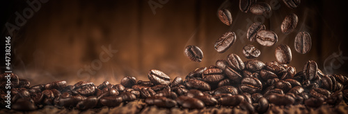 Murais de parede Close-up Of Fresh Roasted Coffee Beans With Smoke Falling Onto Table