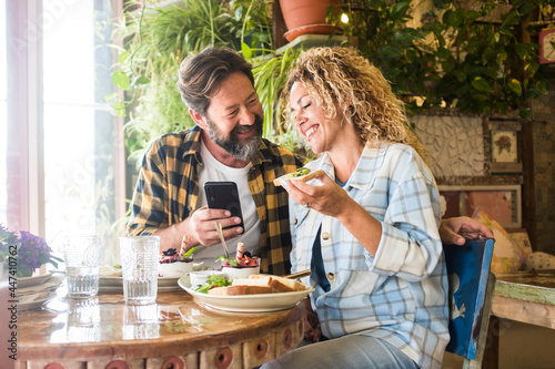 Fototapeta Adult couple smile and enjoy lunch and phone video call sitting at the bar and l