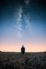 Man Standing On Wheat Field Under The Stars Of The Milky Way At Night. Man Looking At Stars And Dreaming.