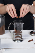 Cropped Shot: Lady In Black Is Making Coffee And Breaking Cinnamon Stick Above French Press With Ground Coffee. The Press Pot Is Made As Glass Bulb In Stainless Body With Handle.