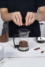 Cropped Shot: Lady In Black Is Making Coffee And Breaking Cinnamon Stick Above French Press With Ground Coffee. The Press Pot Is Made As Glass Bulb In Stainless Body With Black Handle.