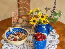 Delicious Breakfast Meal With Fruity Cereal And A Pot Of Vibrant Yellow Daisies On A Round Table