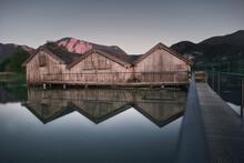 Kochelsee In Den Alpen In Deutschland: Bootshäuser Mit Reflektion, Ruhige Stimmung Bei Sonnenuntergang