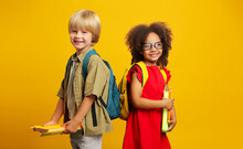 Children With School Backpacks Are Looking At The Camera, Holding Books And Pencils In Their Hands