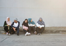 Female Muslim Friends Sitting Together Outdoor