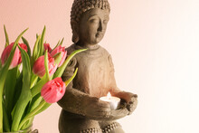 Small Buddha Sculpture Made From Ceramic With A Burning Candle And Pink Tulips Against A Light Background With Copy Space, Selected Soft Focus