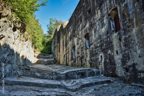 ancient battery on Monte Brione, Italy with stone walls, steps, windows, blue sk Fototapeta