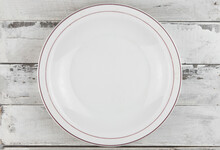 An Empty White Plate On Light Wooden Planks, Natural Wood , Blank Space For Text, Copy Space