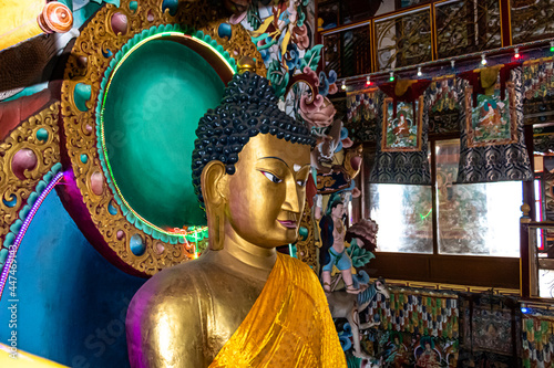 Fotografia huge buddha golden statue decorated with religious flags and offerings at evenin