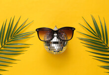 Disco Ball In Sunglasses With Palm Leaves On Yellow Background. Top View. Flat Lay. Minimalism Party Concept