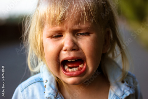 Fotografia Little cute pretty blonde infant girl 3 years old is crying in a summer park