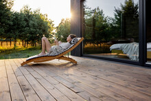 Young Woman Resting On Sunbed And Reading On A Tablet On The Wooden Terrace Near The Modern House With Panoramic Windows Near Pine Forest. Wellness And Mindful Health. Copy Space