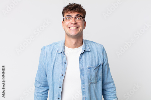 Fotografie, Obraz young handsome man looking happy and goofy with a broad, fun, loony smile and ey