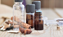 Bottles Of Essential Oil And Empty Graduated Bottle With Spices  On A Wooden Table