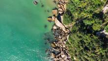 Aerial View Of Waves Hitting Rocks On A Brazilian Beach Coast. Balneario Camboriu