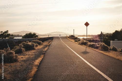 Bike path along Columbia river with bridge in distance #447549712