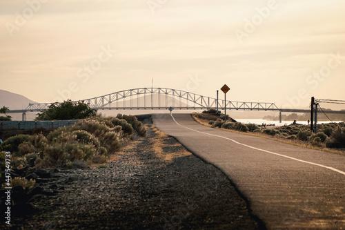 Bike path along Columbia river with bridge in distance #447549733