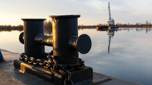 Mooring Bollard On The Mole With Sunset River And Dredger Ship On The Background. Space For Text.