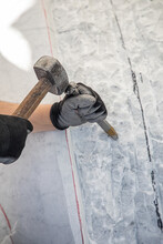 Detail Of Artist's Hands Sculpting Marble With Hammer And Chisel