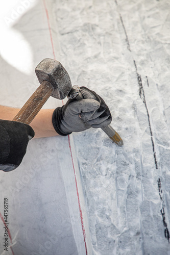 Fotografía Detail of artist's hands sculpting marble with hammer and chisel