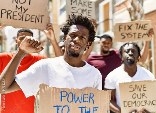 Foto Group of young african american activists holding protest banner protesting at the city