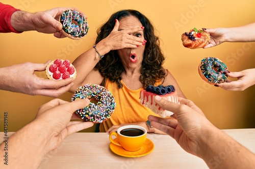 Murais de parede Beautiful middle age woman drinking a cup of coffee around pastries peeking in s