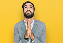 Young Hispanic Man Wearing Business Clothes Begging And Praying With Hands Together With Hope Expression On Face Very Emotional And Worried. Begging.