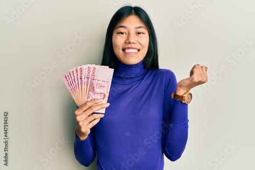 Vászonkép Young chinese woman holding thai baht banknotes screaming proud, celebrating vic