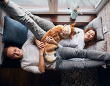 Top view of beautiful couple looking at camera and smiling while lying on widow seat with adorable Corgi. Joyful young woman and man resting with cute dog at home. Concept of relationships and pets.
