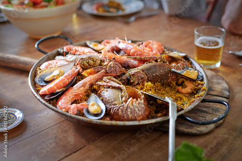 Appetizing seafood paella in pan against beer on table