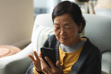 Happy Senior Asian Woman At Home Using Smartphone