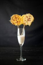 Glass With Rice For Decoration Of Crispy Grated Cheese Chips On Sticks Placed On Black Background
