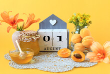 Calendar For August 1 : The Name Of The Month Of August In English, The Numbers 0 And 1, Flowers In Vases, A Jar Of Jam, Apricots On A Gray Napkin, Yellow Background, Side View