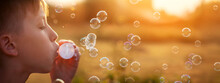 Child Blowing Soap Bubbles On A Summer Day At Sunset Nature.