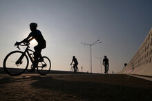 Silhouette Of Three Cyclists Cycling On Road At Sunrise, Indonesia