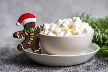 Christmas Gingerbread Man In A Santa Hat Cookie Next To A Cup Of Mini Marshmallows
