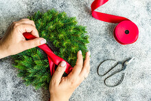 Overhead View Of A Woman Tying A Ribbon On A Fir Wreath