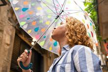 Man Standing Under Umbrella On Rainy Day In City