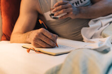 Man Taking Notes In Notebook On Bed