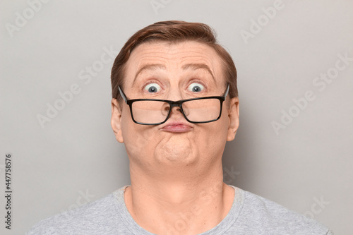 Fototapeta Studio close-up portrait of funny blond mature man with glasses, grimacing and making goofy crazy face, having fun, fooling around