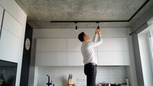 Man Of Caucasian Ethnicity Unscrews A Light Bulb From The Base Of Modern Track Lighting Of A Kitchen At Home. He Looks Like A Professional And Is Neatly Dressed In A Shirt And Trousers