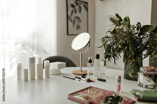 Murais de parede Photo of mirror, face cosmetic, perfumes, eyeshadow palette, lipgloss, makeup brushes, lotion, cream on white dressing table in cozy room